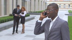 Gruppe glückliche gemischtrassige Wirtschaftler Afroamerikaner, der am Telefon spricht stock video