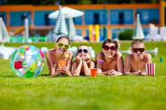 Gruppe glückliche Jugendfreunde, die auf Sommerrasen liegen Lizenzfreies Stockfoto