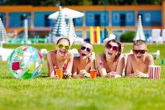 Gruppe glückliche Jugendfreunde, die auf Sommerrasen liegen Lizenzfreie Stockfotografie