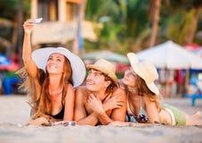 Gruppe glückliche junge Leute, die auf wite liegen, setzen auf den Strand stockfoto