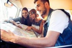 Gruppe glückliche junge Leute in einem Weinlesepackwagen, der eine Straßenkarte betrachtet lizenzfreie stockbilder