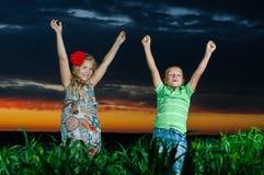 Gruppe glückliche Kinder, die auf Wiese spielen stockfotografie