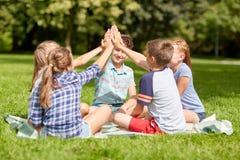 Gruppe glückliche Kinder, die draußen Hoch fünf machen stockfoto