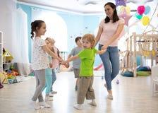 Gruppe glückliche Kinder, die im Kreishändchenhalten, spielend mit ihrem Lehrer im Klassenzimmer stehen lizenzfreie stockfotografie