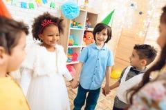 Gruppe glückliche Kinder, die runden Tanz auf Geburtstagsfeier tanzen Konzept von Kind-` s Feiertag lizenzfreies stockfoto