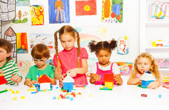 Gruppe glückliche Kinder spielen mit Plastikblöcken stockbild