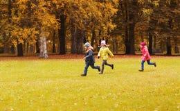 Gruppe glückliche Kleinkinder, die draußen laufen Stockfoto