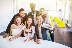 Gruppe glückliche lächelnde Wirtschaftler, die selfie und das Gestikulieren machen Geschäftsteam selfie lizenzfreie stockbilder