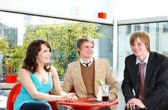 Gruppe glückliche Leute, die im Kaffee sprechen. Stockfotografie