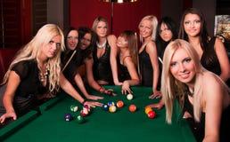 Gruppe glückliche Mädchen, die im Billiard spielen stockbild