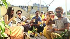 Gruppe glückliche multiethnische Freunde, die mit Cocktails an der Dachspitzenpartei rösten stock footage