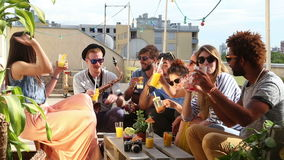 Gruppe glückliche multiethnische Freunde, die mit Cocktails an der Dachspitzenpartei rösten stock video