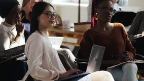 Gruppe glückliche professionelle multiethnische Geschäftsfrauen, die auf Seminarrede am modernen hellen modischen Büroereignis hö stock footage