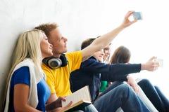 Gruppe glückliche Studenten, die auf einem Bruch nimmt selfie sind Lizenzfreies Stockfoto