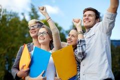 Gruppe glückliche Studenten, die Triumphgeste zeigen Stockbild