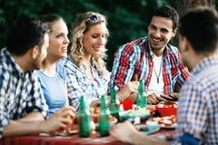 Gruppe glücklichen Menschen, die draußen Lebensmittel essen stockbild