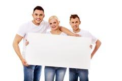 Gruppe glückliche Freunde, die leere Fahne halten Lizenzfreie Stockbilder