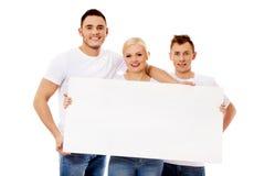 Gruppe glückliche Freunde, die leere Fahne halten Lizenzfreies Stockfoto