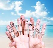 Gruppe glückliche junge Leute am Strand mit Zeichnungsfingersymbol Stockbild