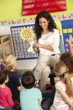 Gruppe grundlegende Alters-Schulkinder in der Klasse mit Lehrer stockfotos