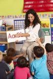 Gruppe grundlegende Alters-Schulkinder in der Klasse mit Lehrer stockbilder
