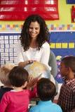 Gruppe grundlegende Alters-Schulkinder in der Klasse mit Lehrer stockbild