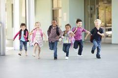 Gruppe grundlegende Alters-Schulkinder, die draußen laufen Stockbild