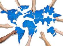 Gruppe Hände, die das Puzzlen bildet Welt halten Stockfotografie
