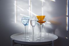 Gruppe hohe langstielige Cocktailgläser in den verschiedenen Formen und in den Farben gefüllt mit klarer Flüssigkeit lizenzfreie abbildung
