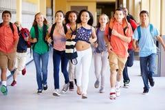 Gruppe hohe Schüler, die entlang Korridor laufen Stockfotografie