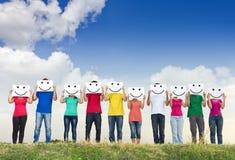 Gruppe Holdingpapiere der jungen Leute mit smiley lizenzfreie stockfotografie