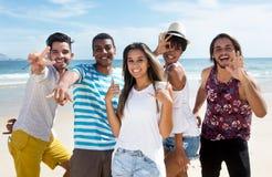 Gruppe internationale junge Touristen, die am Strand tanzen stockfotografie