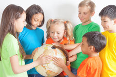 Gruppe internationale Kinder, die Kugelerde halten Lizenzfreie Stockbilder