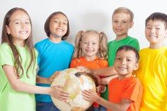 Gruppe internationale Kinder, die Kugelerde halten Lizenzfreies Stockfoto