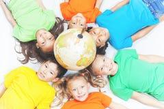 Gruppe internationale Kinder, die Kugelerde halten Stockfotos