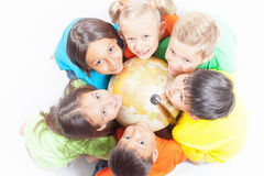 Gruppe internationale Kinder, die Kugelerde halten Stockbild