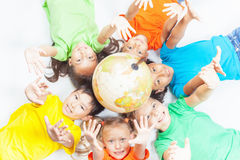 Gruppe internationale Kinder, die Kugelerde halten Stockbilder
