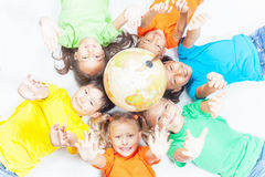 Gruppe internationale lustige Kinder mit Kugelerde Lizenzfreie Stockfotografie