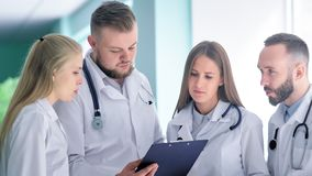 Gruppe Internierten oder junge Doktoren im weißen Laborkittel beraten mit Mentor- oder Leiterarzt stock video footage
