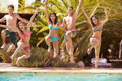 Gruppe Jugendfreunde, die in Swimmingpool springen lizenzfreies stockfoto