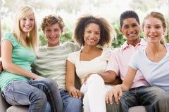 Gruppe Jugendlichen, die auf einer Couch sitzen Stockfotografie