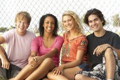 Gruppe Jugendlichen, die im Spielplatz sitzen stockfotografie