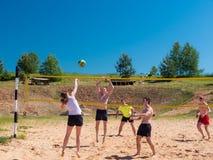 Gruppe Jugendlichen, die voleyball spielen stockbild