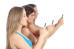 Gruppe Jugendlichmädchen besessen gewesen mit dem intelligenten Telefon Stockbilder