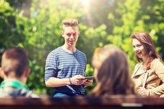 Gruppe Jugendstudenten mit Tabletten-PC outoors lizenzfreies stockbild