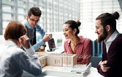 Gruppe junge Architekten mit dem Modell eines Hauses, das im Büro, sprechend arbeitet stockbild