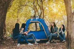 Gruppe junge Asiatinnen, die am Wald kampieren und stillstehen lizenzfreie stockfotografie
