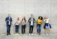 Gruppe junge Erwachsene draußen unter Verwendung der Smartphones, die oben schauen Stockfotos