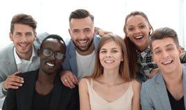 Gruppe junge Führungskräfte, die an der Kamera während eines Arbeit meetin lächeln lizenzfreies stockfoto