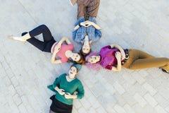 Gruppe junge Frauen der Verschiedenartigkeit, die auf dem Boden liegen und oben schauen lizenzfreies stockbild